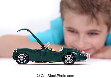 Little boy watching a toy car