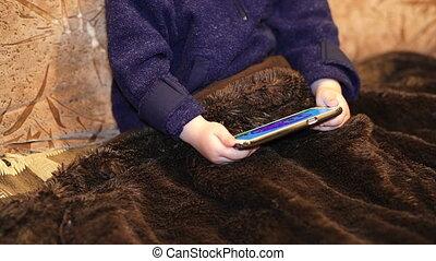little boy watching cartoon on a smartphone indoor