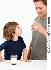 Little boy watching his father drinking milk