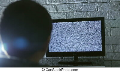 Little boy watching lcd TV in a dark room with loft style brick walls, backside view.