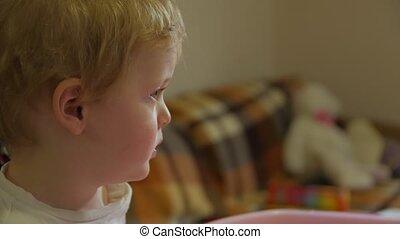 Little boy watching TV side view closeup evening interior