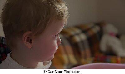 Little boy watching video side view closeup evening interior