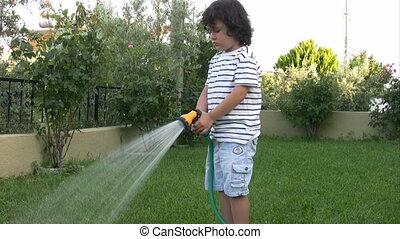 Little boy watering garden