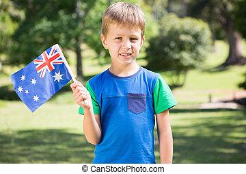 Little boy waving australian flag on a sunny day