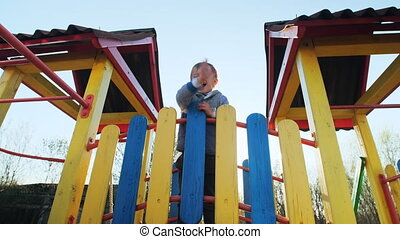 Little boy waving his hand at camera and smiling at playground at sunset