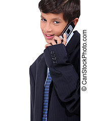 Little boy wearing a business suit and chatting on a cellphone