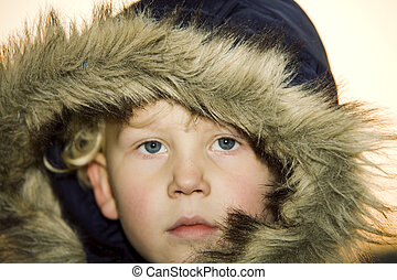 Little boy wearing a fur lined hood