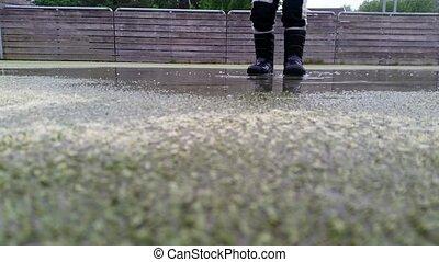 Little boy wearing black rubber boots, jumping of joy in a...