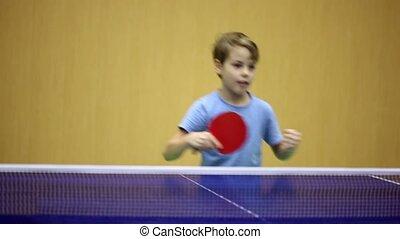 Little boy wearing blue shirt playing ping pong