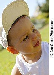Little boy wearing cap in the garden