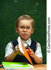 Little boy wearing glasses posing with stationery