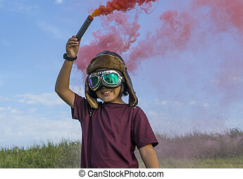 Little boy wearing helmet and aircraft googles standing on a green field with colorful smoke, pretending to be a pilot