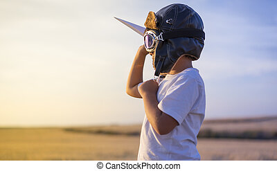 Little boy wearing helmet and dreams of becoming an aviator while playing a paper plane at sunset