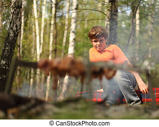 Little boy wearing in orange t-shirt sits near campfire; grill and barbecue