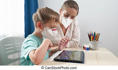 Little boy wearing protective medical mask respirator studying in classroom with female teacher. Doing homework and studying at home with parents during lockdown and self isolation