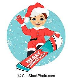 little boy wearing santa claus costume snowboarding over...