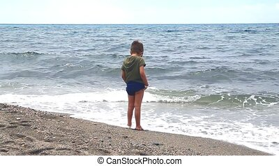 little boy wets his feet in the sea