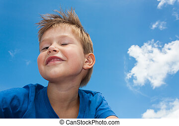 Cute and gorgeous little boy against blue sky with white clouds smiling and winking with cheeky look on his friendly face