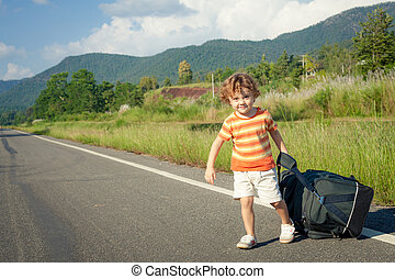 little boy with a big bag goes on the road in the daytime