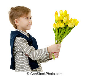 Little boy with a bouquet of flowers tulips.
