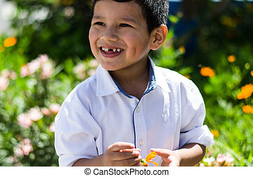 Little boy with a daisy in his hand and laughing