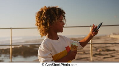 Little boy with a ice cream using phone - Side view of mixed...