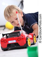 Little boy with a radio controlled car