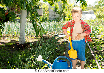 Little boy with a spade in the garden