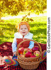 Little boy with apple in autumn