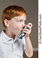 Little boy with asthma using his inhaler
