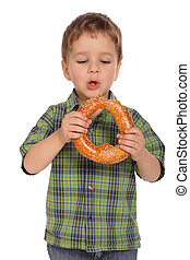Little boy with bagel, isolated on white