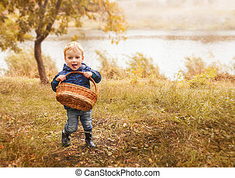 Little boy with basket in autumn forest