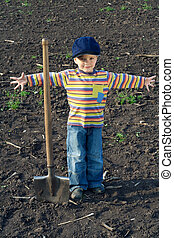 Little boy with big shovel in the field
