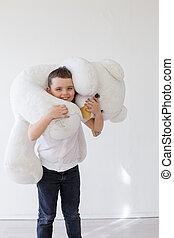 Little boy with big soft bear toy