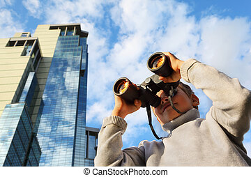 Little boy with binoculars outdoor; modern skyscrapers, blue sky with white clouds