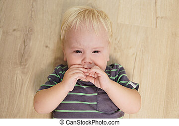 Little boy with blond hair cries on the floor