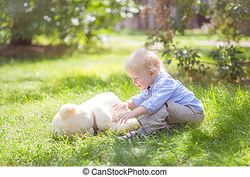 little boy with blond hair playing with a teddy bear in the green grass