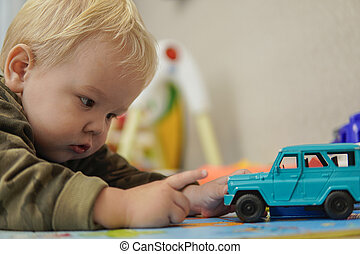 Little boy with blond hair playing with blue car
