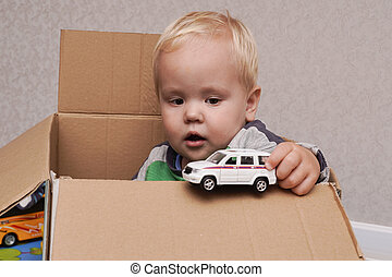Little boy with blond hair sitting in a box