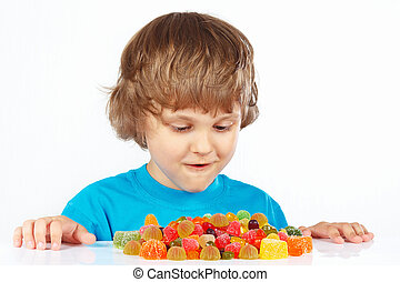 Little boy with candies on white background