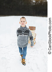 Little boy with Christmas present boxes on wooden sled in snow. Little boy with sledge in snowy forest. Winter holidays decoration. Child with sleigh. Kid sledding.