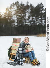 Little boy with Christmas present boxes sitting on wooden sledge in snow. Little boy with sledge in snowy forest. Winter holidays decoration. Child with sleigh. Kid sledding.