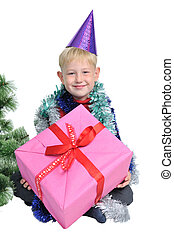 Little boy with Christmas present near new year tree