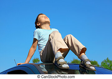 little boy with closed eyes sitting on car roof on blue sky