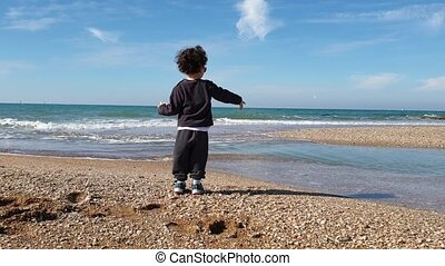 Little boy with curly hair playing at the beach