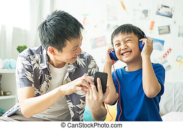 Little boy with dad listening to music on bed in bedroom