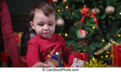 Little boy with dark hair, wearing a red sweater, deer playing with yellow shiny Christmas garland, he knocks on her his little hand, and later parents help him, pulling out of the box toys