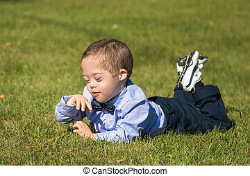 Little Boy with Down syndrome lying on Grass