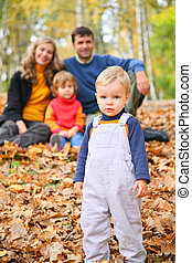 Little boy with family in forest in autumn