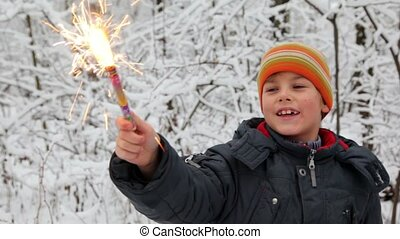 Little boy with firework in snow forest